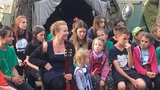 Grupa dzieci i opiekun siedzących na ławkach przed namiotem